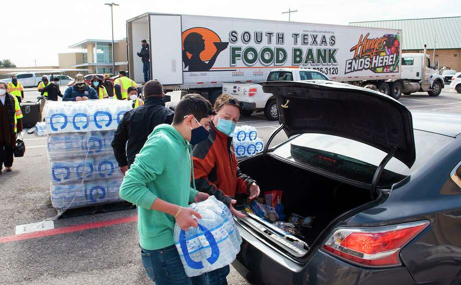 City of Laredo workers and volunteers help load cases of water, loaves of bread and packs of snacks into cars on Tuesday, Feb. 16, 2021, as Laredoans without water or electricity pick up the essentials distributed by the South Texas Food Bank in partnership with the City of Laredo at Nixon High School. Photo: Danny Zaragoza / Laredo Morning Times