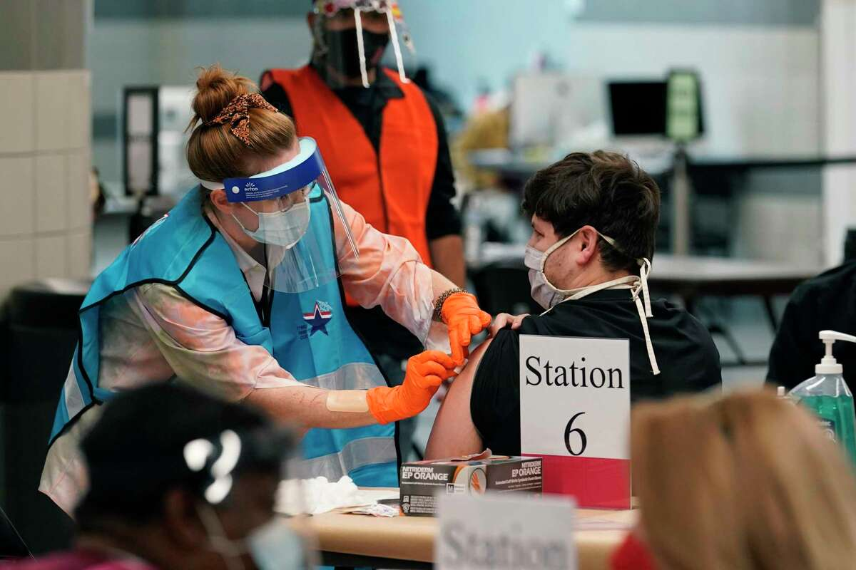 A health care worker administers a COVID-19 vaccination at the new Alamodome COVID-19 vaccine site on Jan. 11, 2021. Moving your arm around after the injection can increase blood flow and prevent injection site soreness.