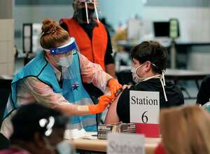 A health care worker administers a COVID-19 vaccination at the new Alamodome COVID-19 vaccine site on Jan. 11, 2021. Second-dose vaccines resumed Friday but there are no first-dose appointments available yet. The city hasn't received a new shipment of first doses to administer at the central vaccination site in more than three weeks.