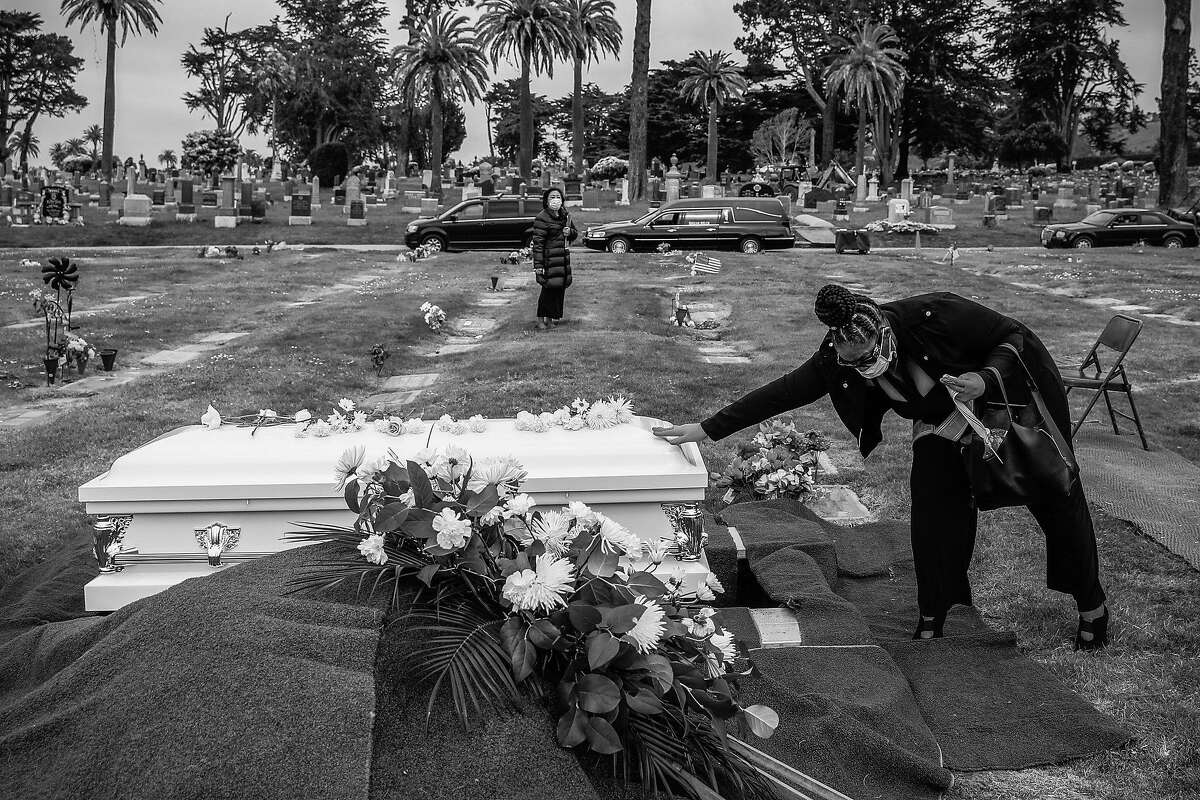 Debra Holloway prays over her mother Tessie Henry's casket before saying goodbye to her after she died of COVID-19 at age of 83 on Wednesday, April 8, 2020 in Colma, California. Tessie Henry loved funerals. So much so that her children called her a