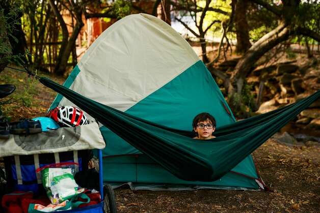 """Theo Schrager, 6, relaxes in his hammock that he """"loves"""" outside the tent he is living in with his mom Leah Naomi Gonzales (not pictured) in Berkeley, California, on Monday, Aug. 19, 2019. They have been living in a tent at Strawberry Creek Park for months after being unable to secure money for a hotel.   Theo: Homeless at age 7: All 7-year-old Theo wants is his own room and a kitchen to bake a chocolate cake. He dreams about it while he sleeps in tents, in parks and under the freeway in Berkeley, California. Theo and his mother Leah have been homeless for much of his life. During the pandemic, Theo's life was devoid of structure. No school meant hours on the computer and erratic outbursts. After a year of ping-ponging between hotels and the streets, they ended up in a tent on the same block they started out on - outside a Tesla dealership. Theo's struggle, even amidst the affluent community of Berkeley, shows – the intractability of California's homeless crisis. Photo: Gabrielle Lurie"""