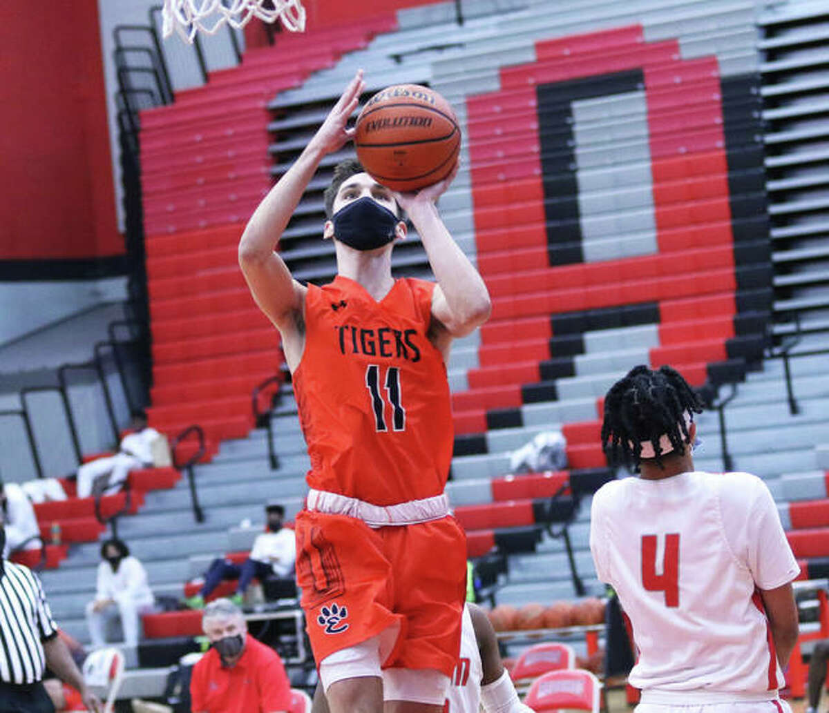 Edwardsville's Brennan Weller (11) sidesteps Alton's Lathan O'Quinn and scores two of his 30 points in Saturday's SWC win over the Redbirds at Alton High in Godfrey. Weller joined the Tigers' 1,000-points club with his 14th point in the game.