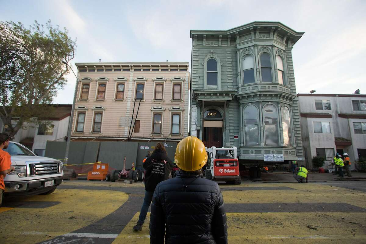 A Victorian home (left), originally located on Franklin Street was moved to its new location to Fulton Street in San Francisco, Calif., on Feb. 21, 2021.