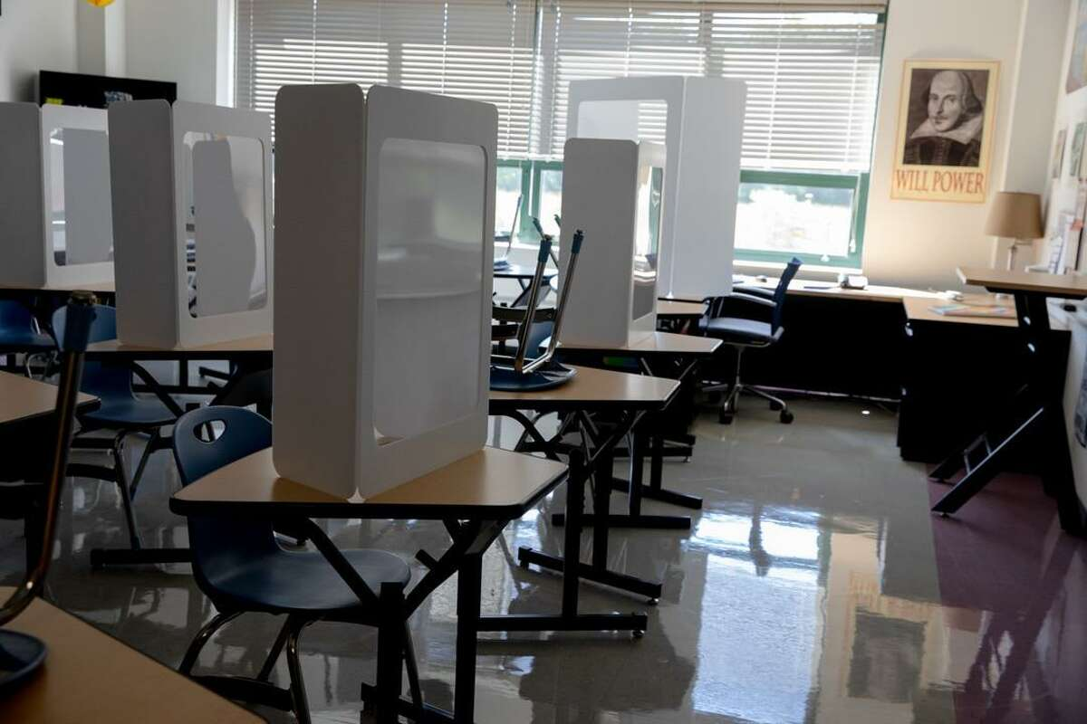 A classroom is set up for the fall semester at Middletown High School. There will be an empty desk between two students. High school students will have to carry their desk shield assigned to them when moving to another class and submit it at the end of the day for sanitization.