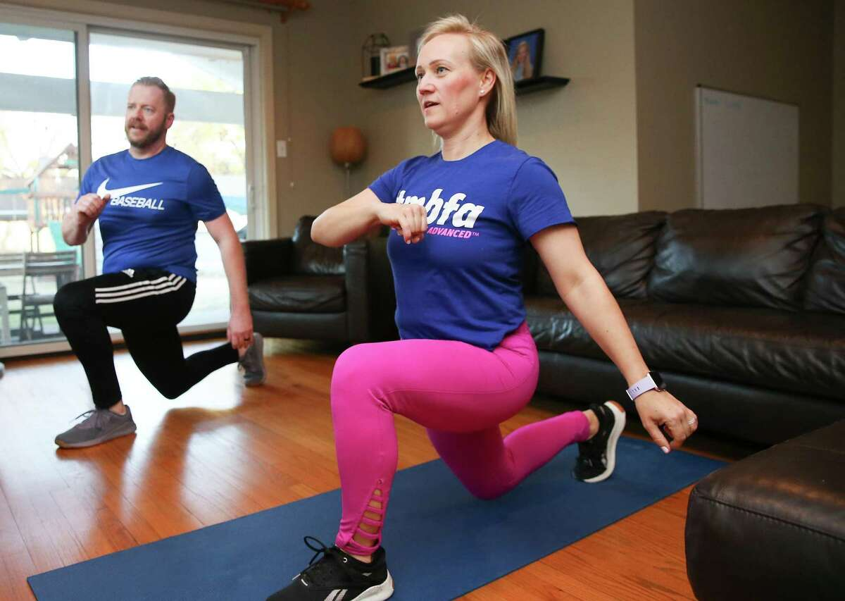 Barbara and Kyle Smith work out in their home to Beach Body workouts in Houston on Friday, Feb. 19, 2021.
