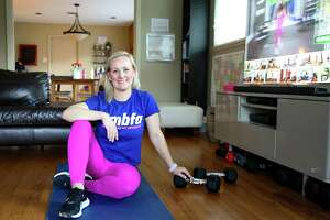 Barbara Smith sits where she works out in her living room in Houston on Friday, Feb. 19, 2021. Smith had always preferred running, but since the pandemic has been working out at home and has lost over 20 pounds.