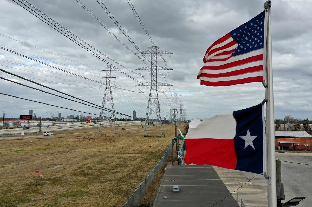 HOUSTON, TEXAS - FEBRUARY 21: The U.S. and Texas flags fly in front of high voltage transmission towers on February 21, 2021 in Houston, Texas.