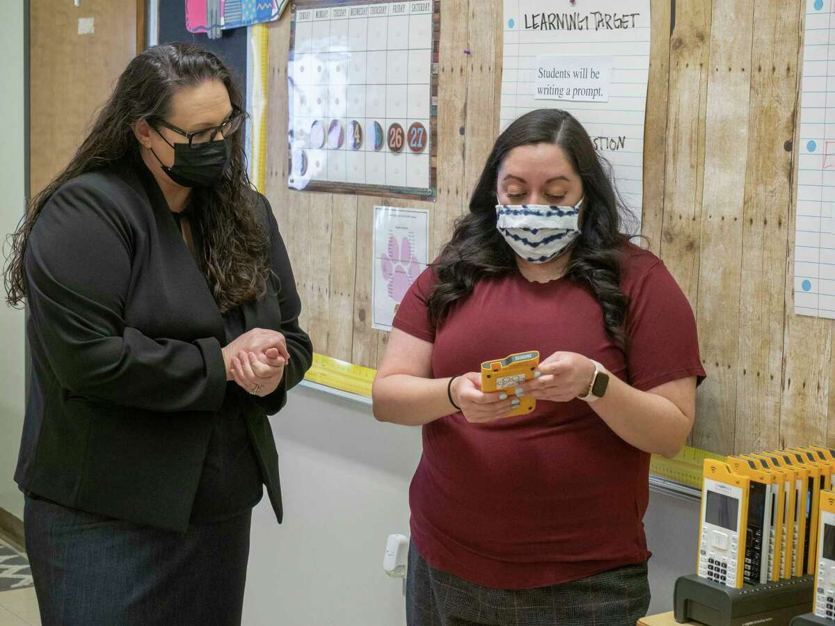 In this picture Midland High geometry and algebraic reasoning teacher Maricela Quezada (right) shows off the new computer integrated calculators students can use to her former teacher, MISD Superintendent Angelica Ramsey, at Midland High School.