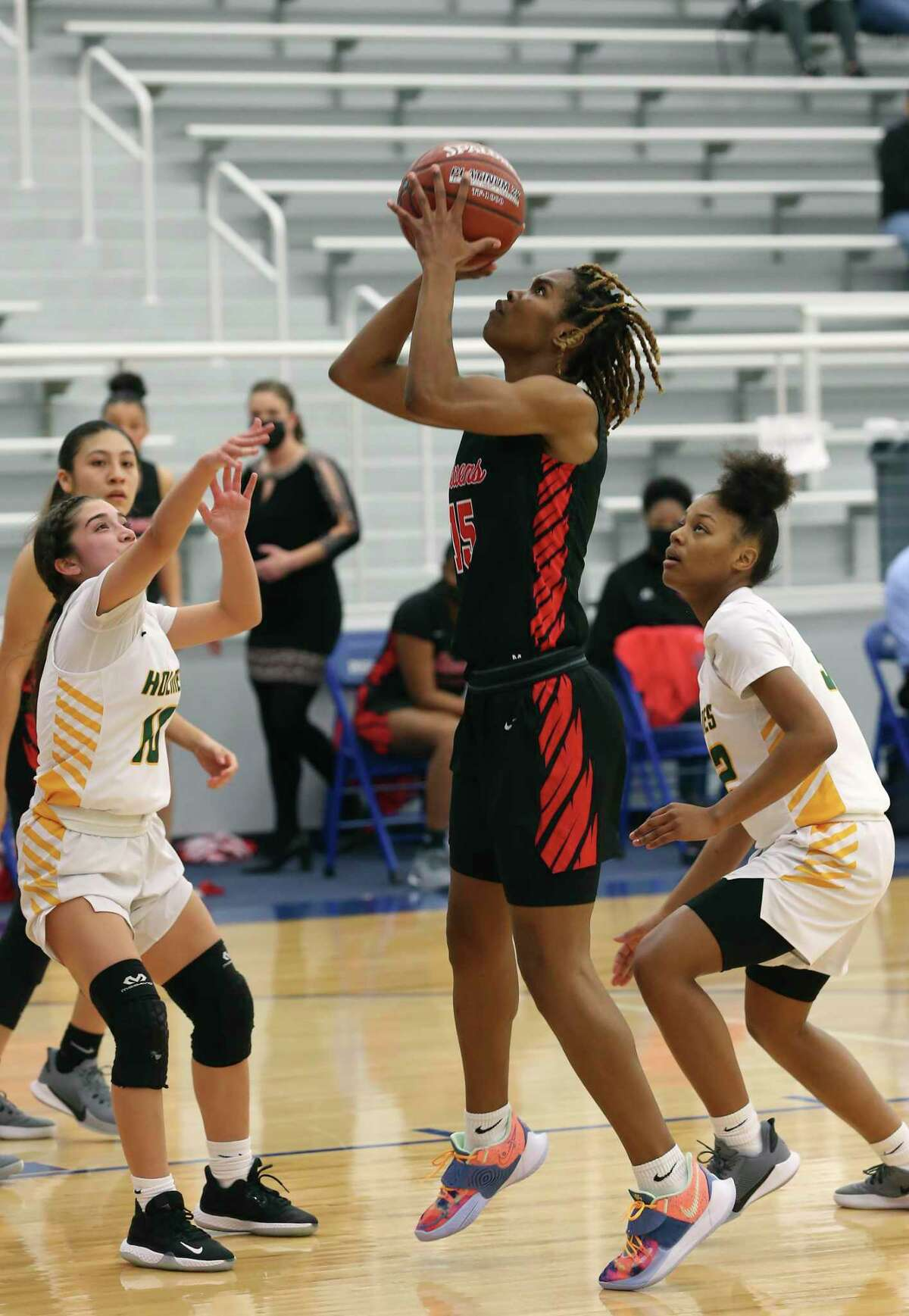Stevens Semaj Adams shoots between Holmes' Sydney Ceciliano, left, and Miyana Bailey at Harlan High School Gym, Wednesday, Jan. 13, 2021. Stevens went on to win, 51-36. Adams ended the game with 19 points.