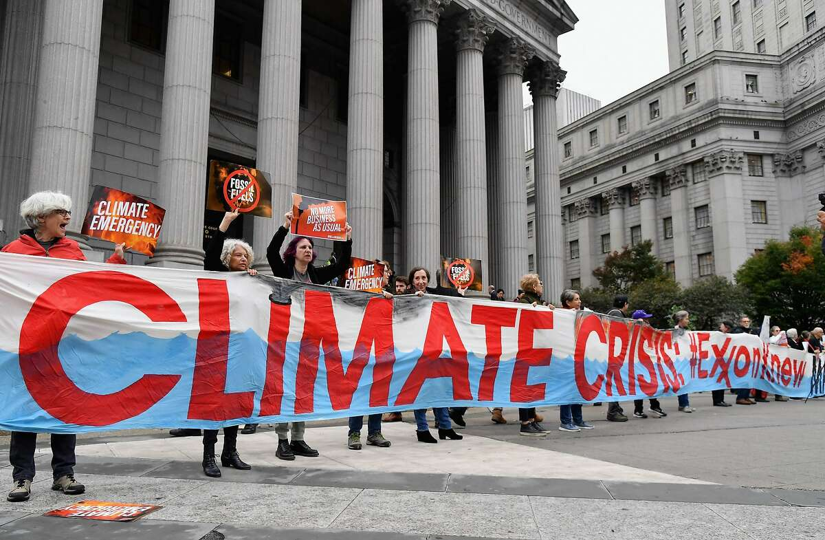 (FILES) In this file photo taken on October 22, 2019 climate activists protest on the first day of the Exxon Mobil trial outside the New York State Supreme Court building in New York City. - Exxon Mobil plans to announce new steps to tackle climate change -- including by adding members to its board -- as it confronts rising investor scrutiny of its contribution to global emissions, US media reported on January 27, 2021. (Photo by Angela Weiss / AFP) (Photo by ANGELA WEISS/AFP via Getty Images)