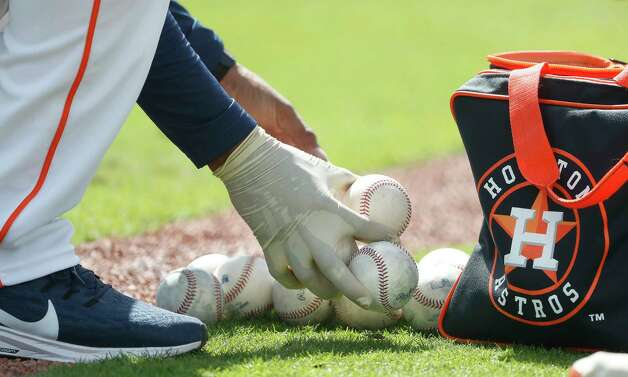 A coach wearing gloves picks up baseballs during the first full squad workouts for the Astros, in West Palm Beach, Florida, Monday, February 22, 2021. Photo: Karen Warren, Staff Photographer / @2021 Houston Chronicle