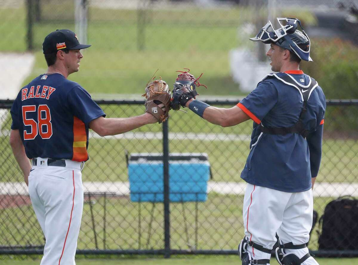 Houston Astros catcher Jason Castro glove bumps pitcher Brooks Raley (58) after Raley threw a bullpen session during the first full squad workouts for the Astros, in West Palm Beach, Florida, Monday, February 22, 2021.