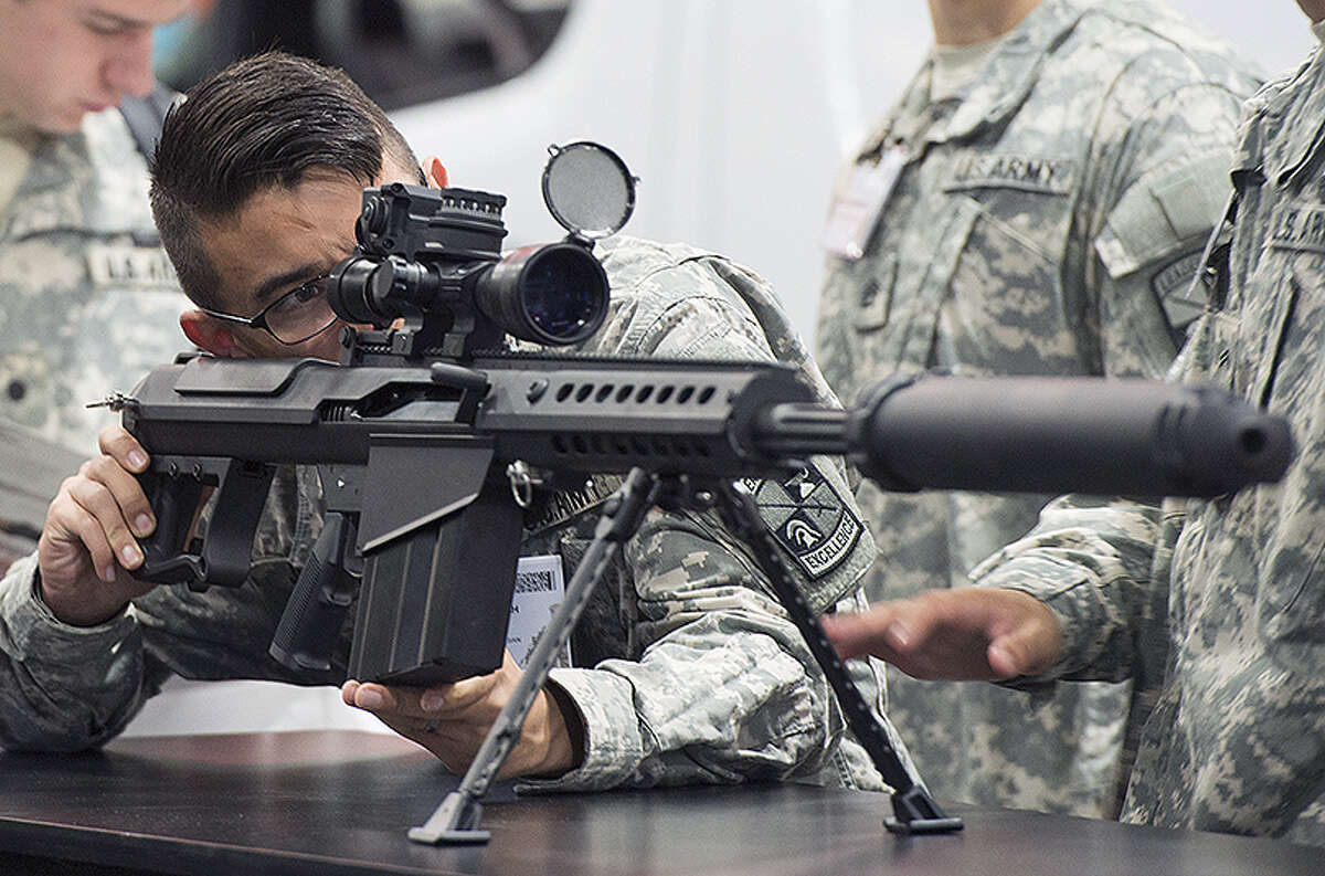 An Army soldier looks over a Barrett M107A1 rifle, which is designed to be used with a suppressor, during an exposition.