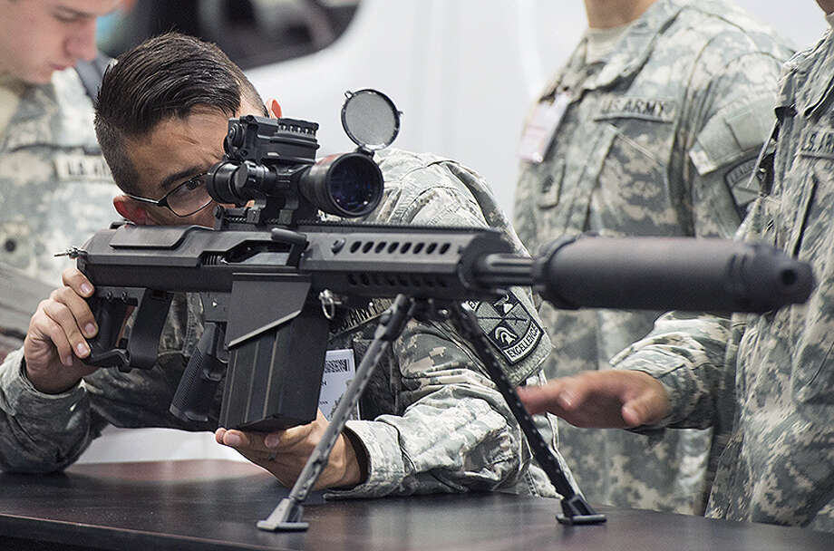 An Army soldier looks over a Barrett M107A1 rifle, which is designed to be used with a suppressor, during an exposition. Photo: Jim Watson   AFP Via Getty Images