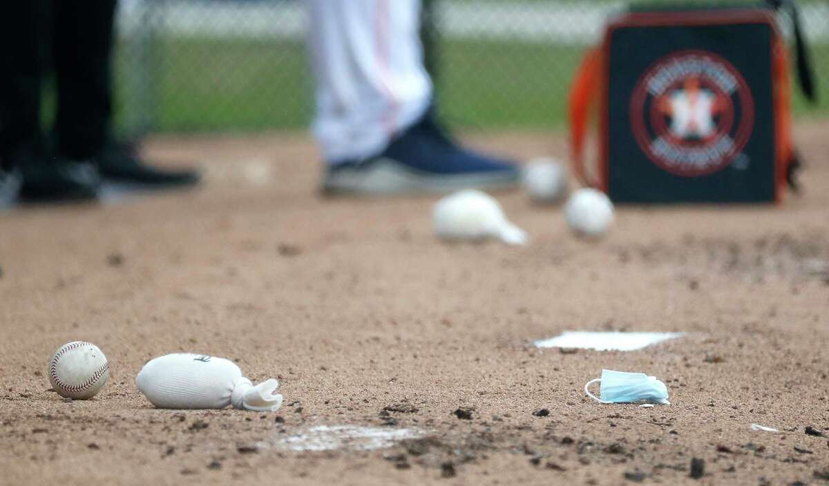 A discarded mask lies next to a baseball and rosin bag during a bullpen session during the first full squad workouts for the Astros, in West Palm Beach, Florida, Monday, February 22, 2021.