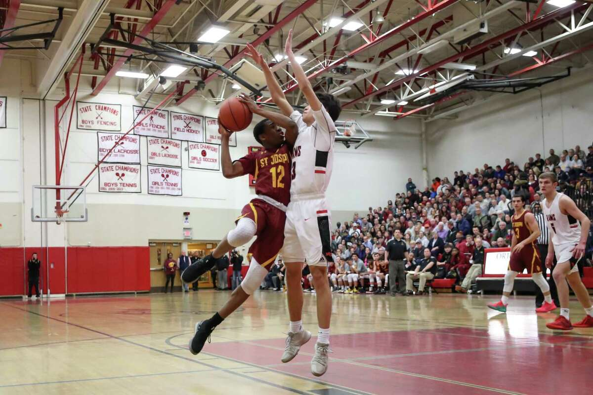 Jason James (12) of St. Joseph drives the net hard while being defended by New Canaan's Ben Sarda (3) during the Division IV Semi Final game between St. Joseph High School Boys Varsity Basketball and New Canaan Boys Varsity Basketball on March 12, 2019 at Warde - Fairfield High School in Fairfield, CT.