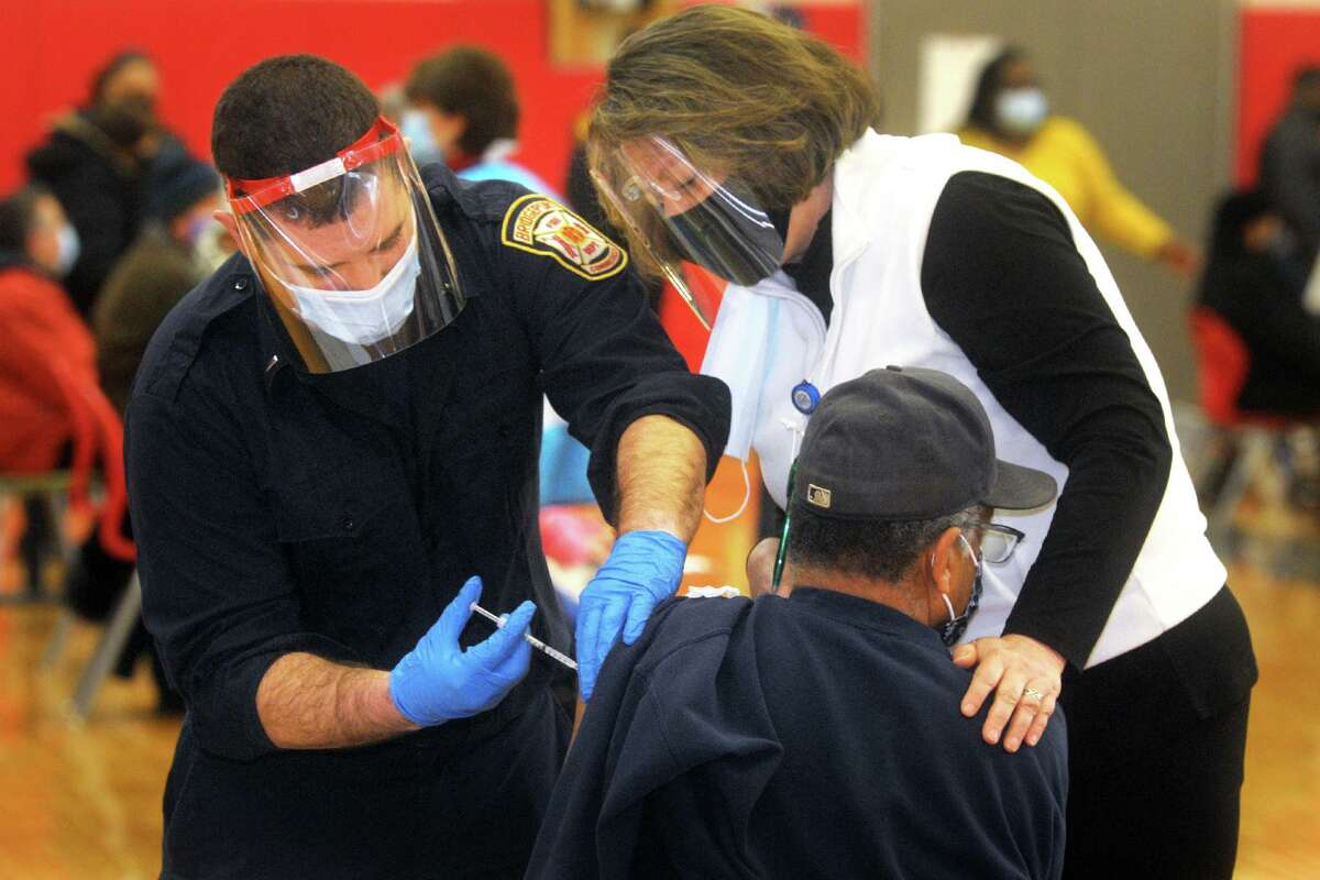 Nurse Elin Loh assists Lt. Ken Benedict of the Bridgeport Fire Department as he administers a COVID-19 vaccination to a man at the weekly vaccination clinic held in the gymnasium of Central High School, in Bridgeport Feb. 10.