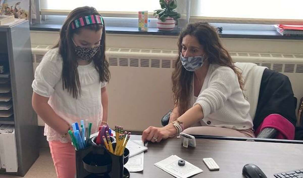 Tina Taylor, a third grade teacher at Mohegan School, works with Samantha Deming.