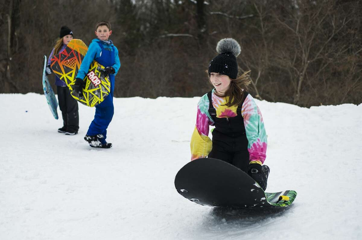 Cameron Dryer, 11, right, jumps onto her sled at the top of the sledding hill at City Forest while Reid Dryer, 9, center, and Leighton Palmer, 9, left, watch Monday afternoon, Feb. 22, 2021 in Midland. Midland Public Schools and several other local school districts closed on Monday due to inclement weather. (Katy Kildee/kkildee@mdn.net)