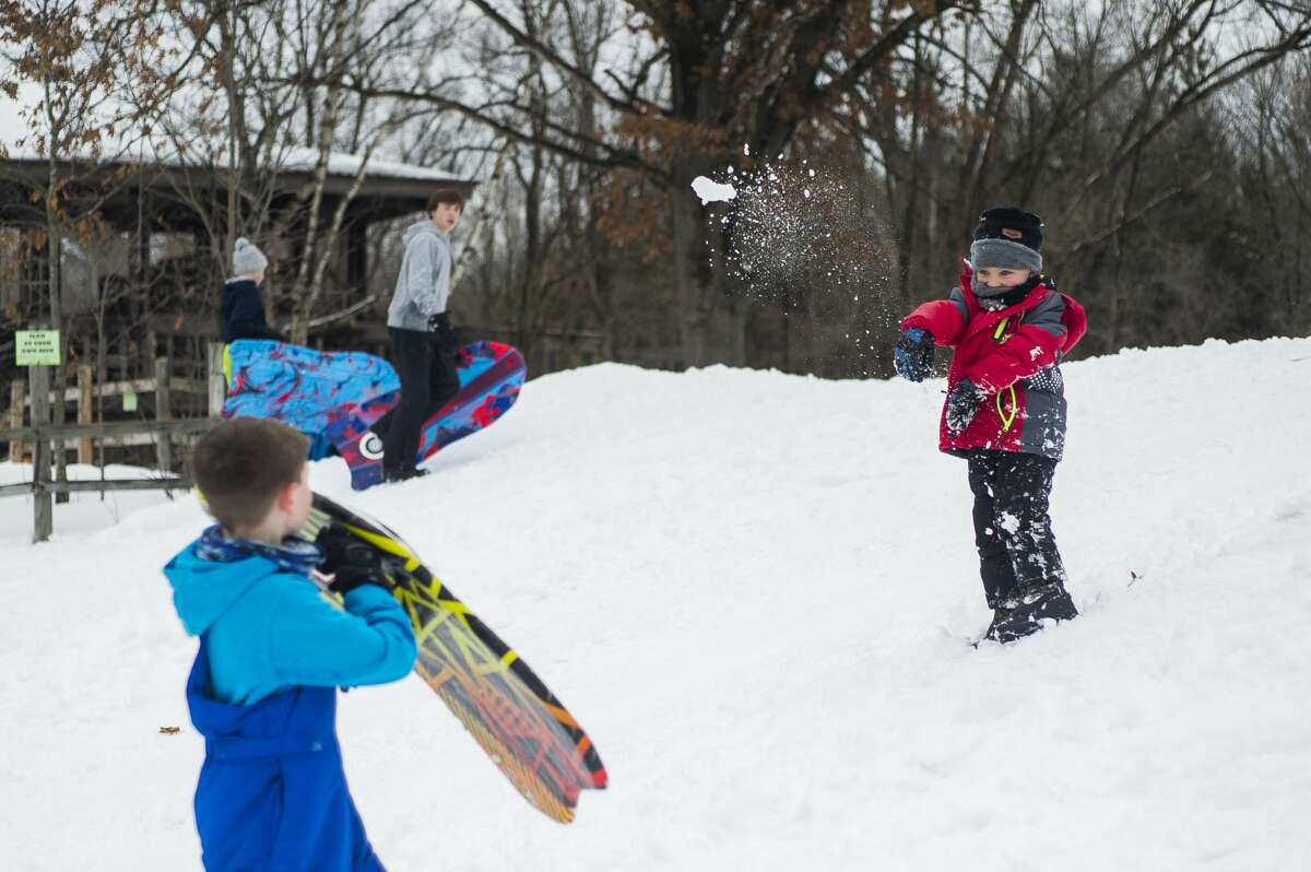Konnor Dillon, 4, right, tosses a snowball towards Reid Dryer, 9, left, while they play on the sledding hill at City Forest Monday afternoon, Feb. 22, 2021 in Midland. Midland Public Schools and several other local school districts closed on Monday due to inclement weather. (Katy Kildee/kkildee@mdn.net)