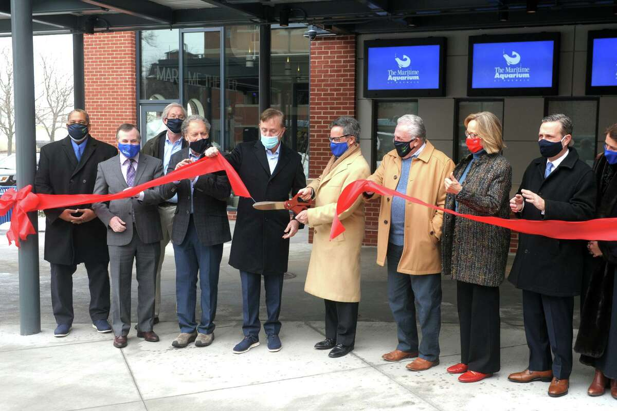 Jason Patlis, President and CEO of The Maritime Aquarium is joined by Gov. Ned Lamont and other state and community leaders as he cuts the ribbon during an opening ceremony for the aquarium's new 4D movie theater, in Norwalk, Conn. Feb. 22, 2021.