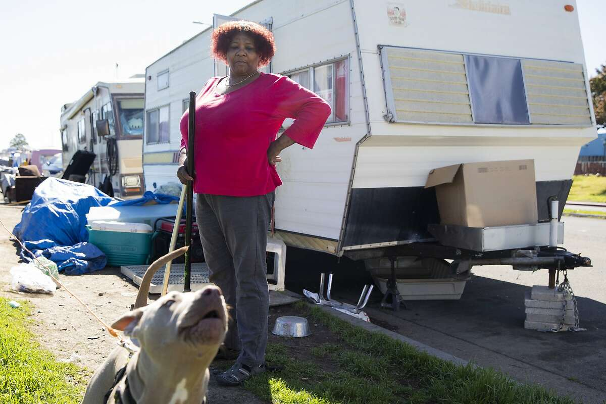 Amilee Smith, 60, cleans up the area outside her RV with her dog Mimi while parked at an RV encampment along Rydin Road in Richmond.