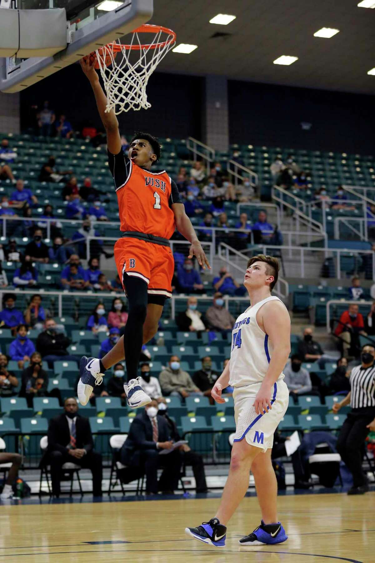 Bush's Zion Bourgeois (1) lays up a shot past Katy Taylor's Nolan Hay (54) during the second half of a 6A district boys high school basketball playoff game Saturday, Feb. 20, 2021 at the Merrell Center in Katy, TX.