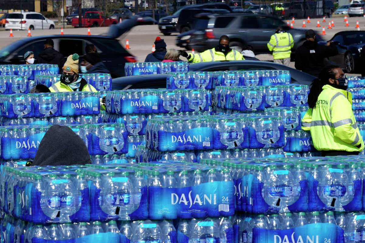 Cases of water are loaded into cars at a City of Houston water distribution site Friday, Feb. 19, in Houston. The drive-thru stadium location was setup to provide bottled water to individuals who need water while the city remains on a boil water notice or because they lack water at home due to frozen or broken pipes.