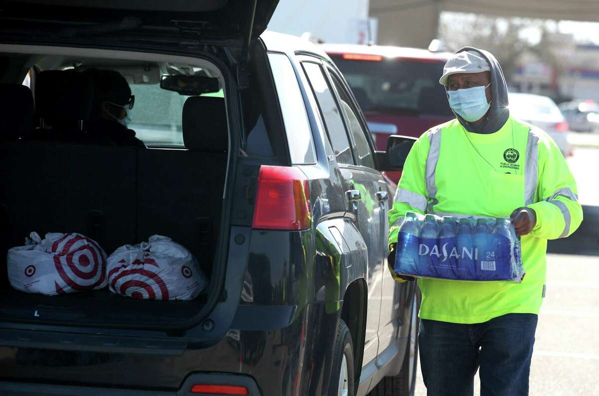 Workers with Houston Public Works prepare to load cases of water into waiting cars during a mass water distribution at Delmar Stadium on Feb. 19 in Houston.