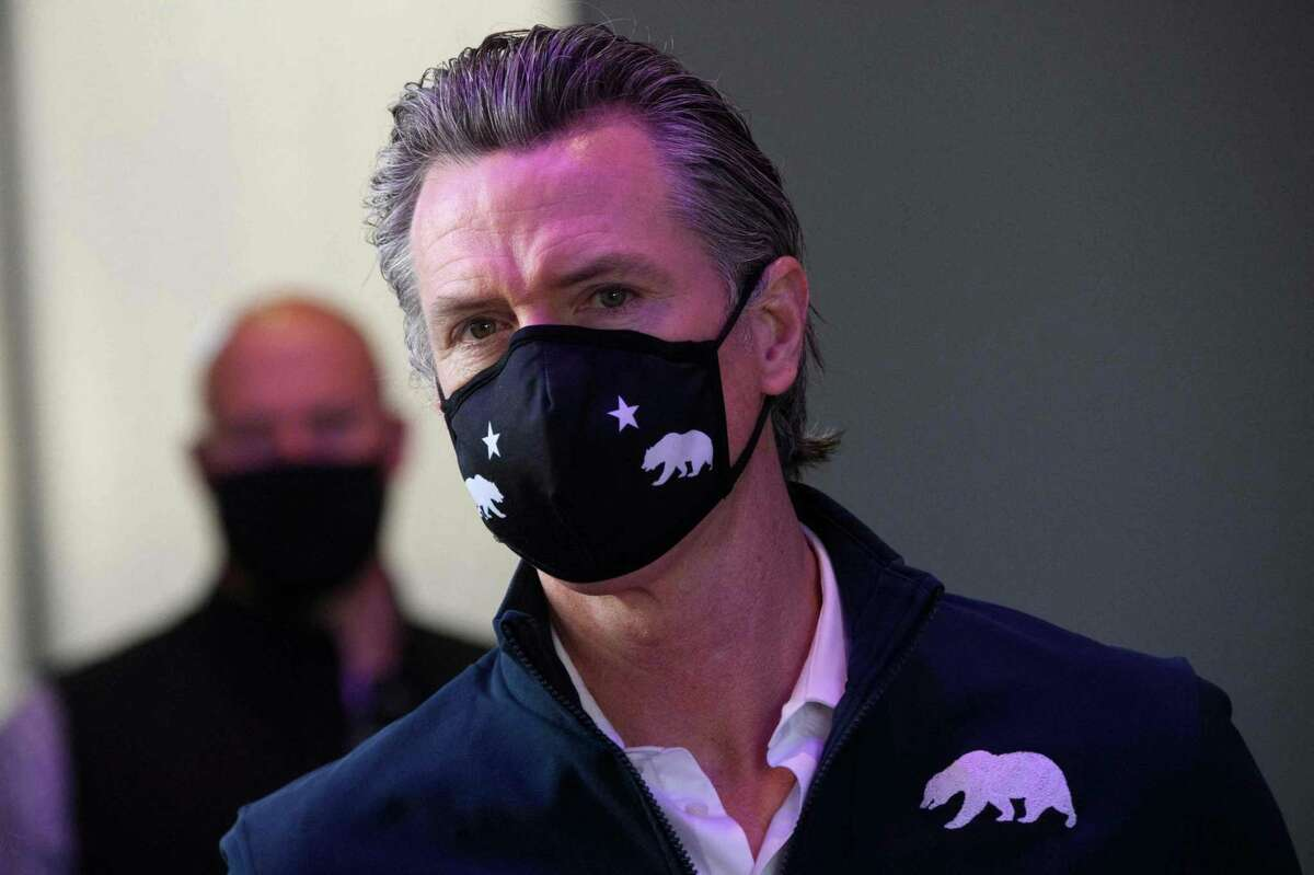 California Gov. Gavin Newsom wears a face mask as he prepares to give a briefing after touring a COVID-19 vaccination site on Feb. 22, 2021, in Long Beach, Calif.