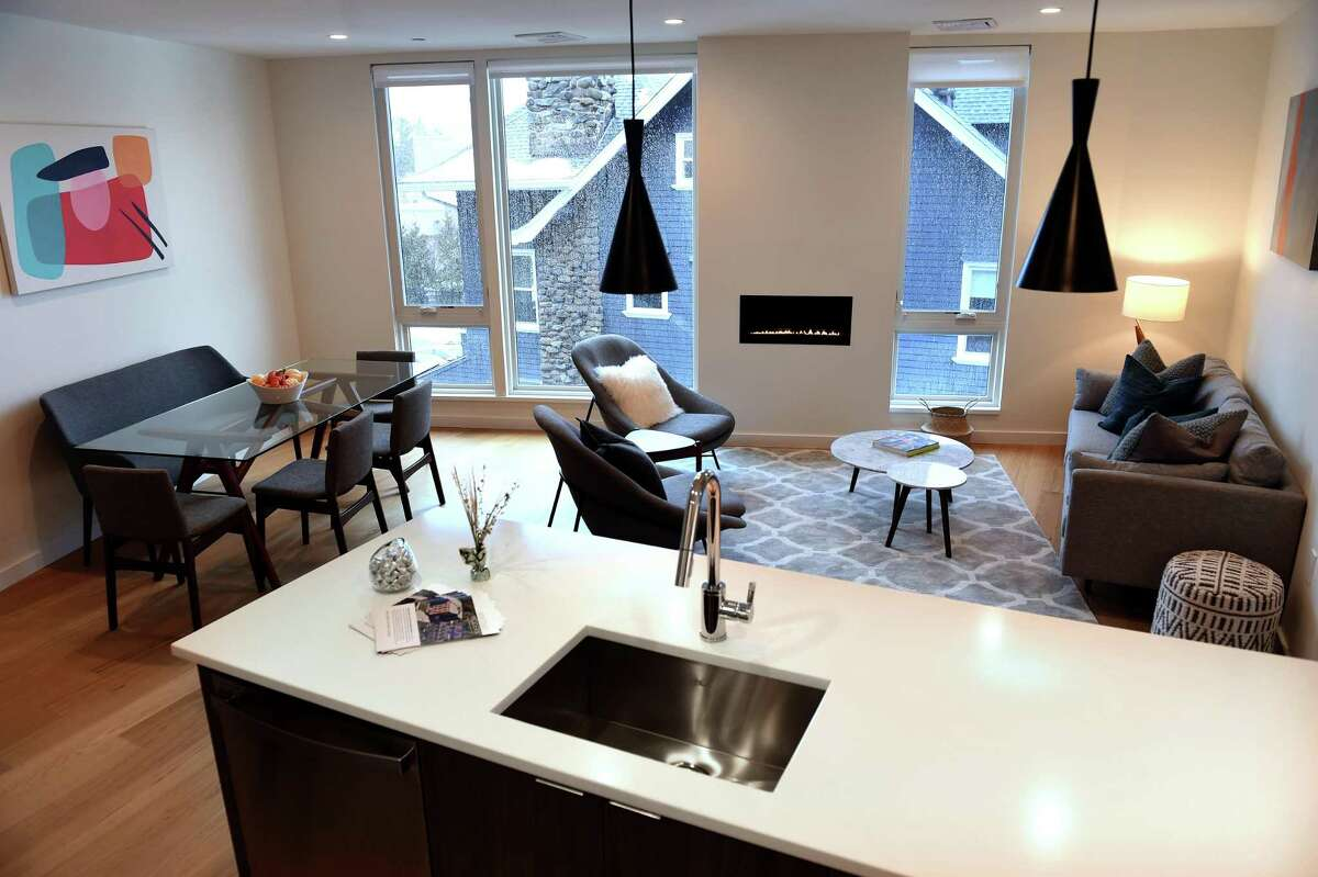 The living room/dining room/kitchen in an open floor of a two-bedroom apartment at the Whitney Modern in New Haven on Feb. 22, 2021. A 1,003-square-foot, two-bedroom and two-bathroom unit in the building can be rented for $2,950 a month, said leasing manager Kristen Perkins. According to the Whitney Modern's website, the least expensive unit available is a 632-square-foot, one-bedroom apartment for $1,840 monthly. The units boast floor-to-ceiling windows and hardwood floors. Greenberg said the units in the building follow an open-floor plan. According to Greenberg, all but 11 of the units in the Modern are currently leased. The units range from 632 to 1,203 square feet.