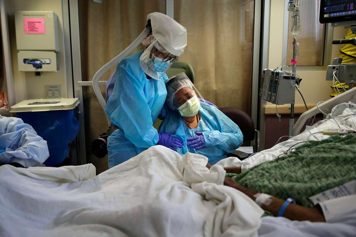 Romelia Navarro, right, is comforted by nurse Michele Younkin, left, as she weeps while sitting at the bedside of her dying husband, Antonio Navarro, in St. Jude Medical Center's COVID-19 unit in Fullerton, Calif., July 31, 2020. (AP Photo/Jae C. Hong)
