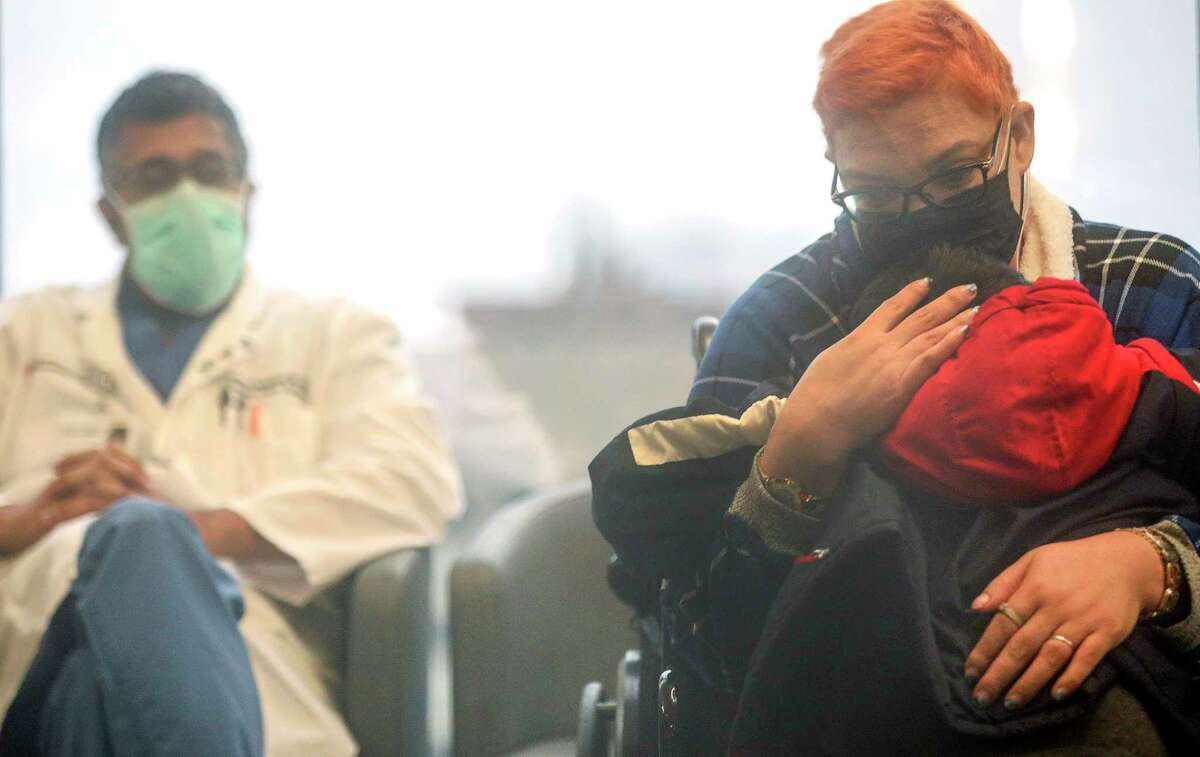 Crystal Gutierrez holds her son Angel, 4, during a press conference to meet and thank Dr. Keshava Rajagopal, left, nurses and hospital staff for helping her battle COVID-19 on Friday, Feb. 12, 2021, at Houston Heart in Houston.