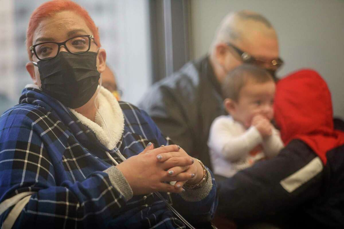 Crystal Gutierrez, left, pauses to reflect as she thanks doctors, nurses and hospital staff for helping her battle COVID-19, while her husband holds their sons, during a press conference Friday, Feb. 12, 2021, at Houston Heart in Houston.