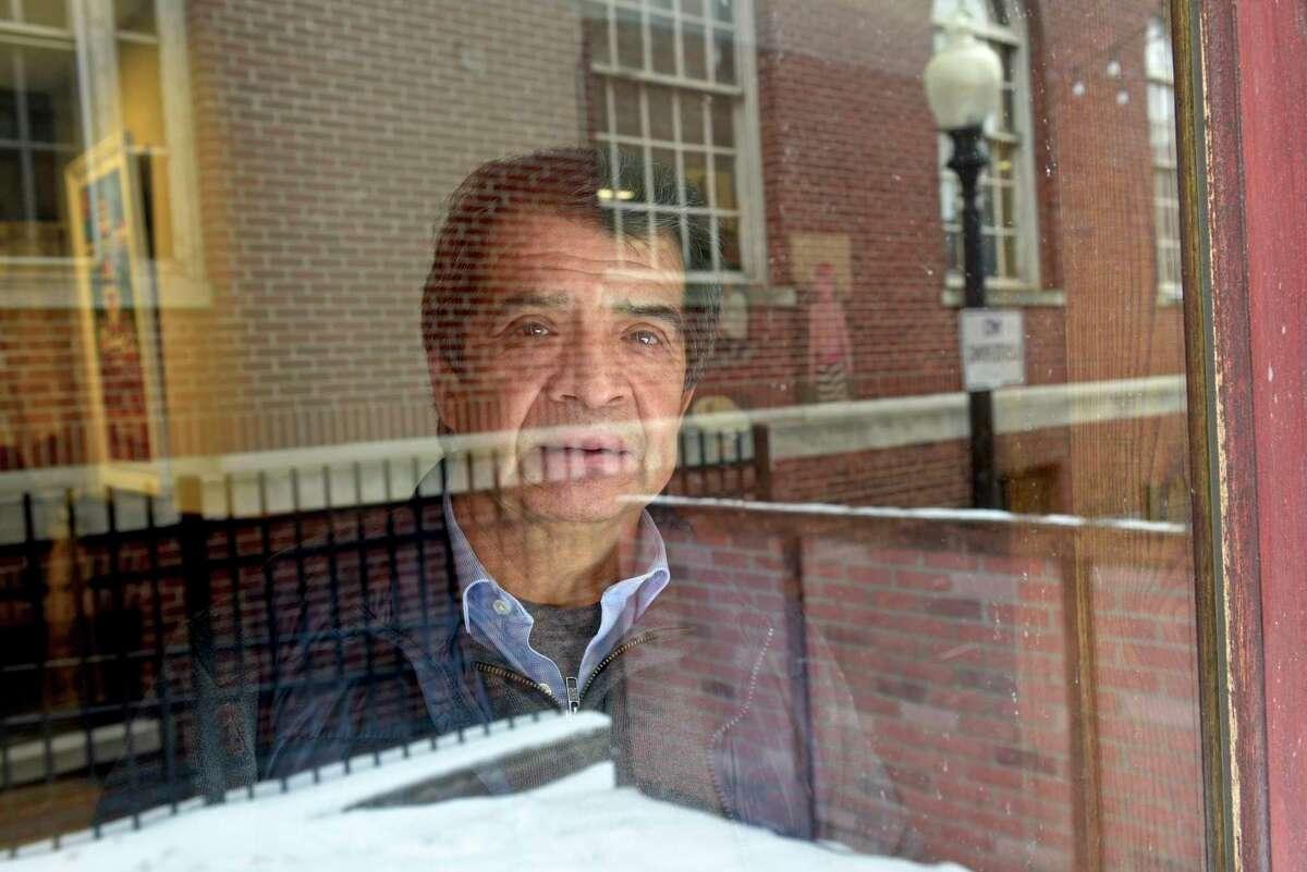 Wilson Hernandez, owner of La Mitad del Mundo restaurant looks through a dining room window. Monday, February 22, 2021, in Danbury, Conn.