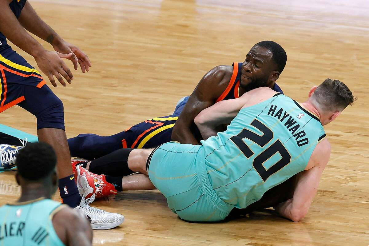 Draymond Green #23 of the Golden State Warriors battles for possession with Gordon Hayward #20 of the Charlotte Hornets during the fourth quarter of their game at Spectrum Center on February 20, 2021 in Charlotte, North Carolina.