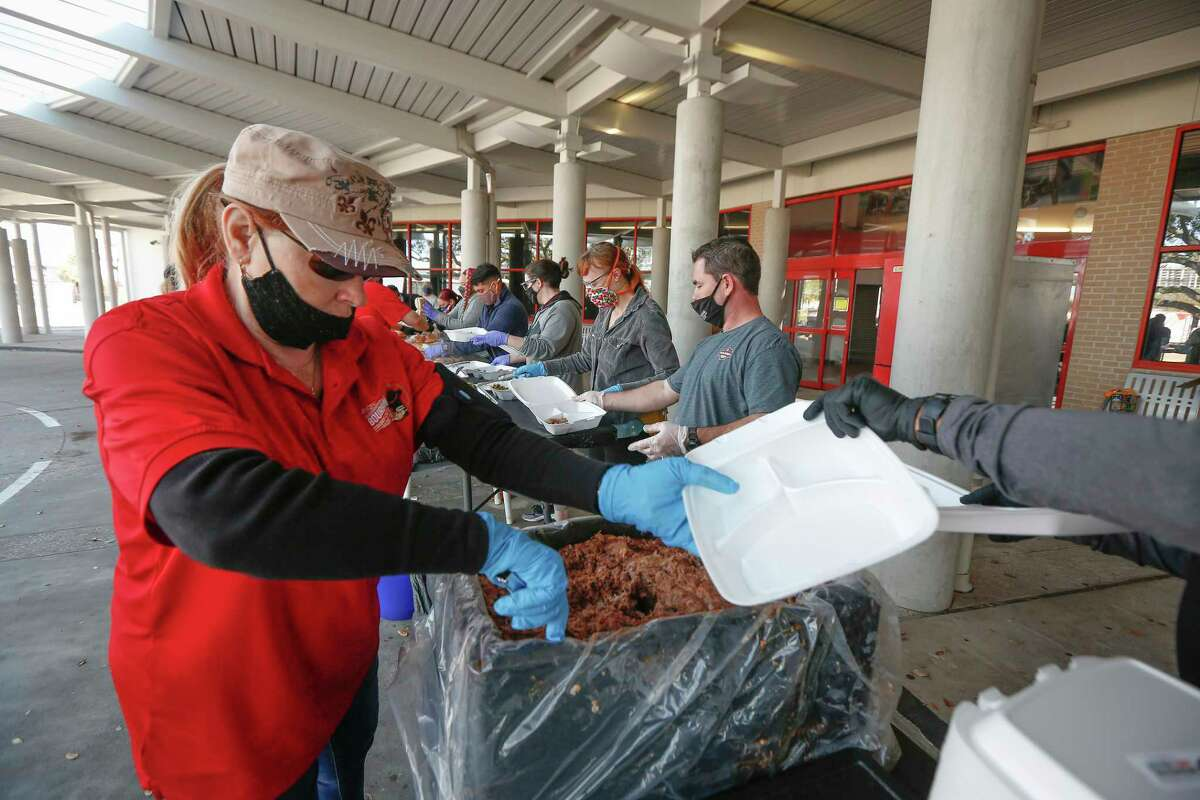 Patti Dunn helps in Operation BBQ Relief food line as they prepare meals and Crowd Source Rescue will distribute them Monday, Feb. 22, 2021, in Houston.
