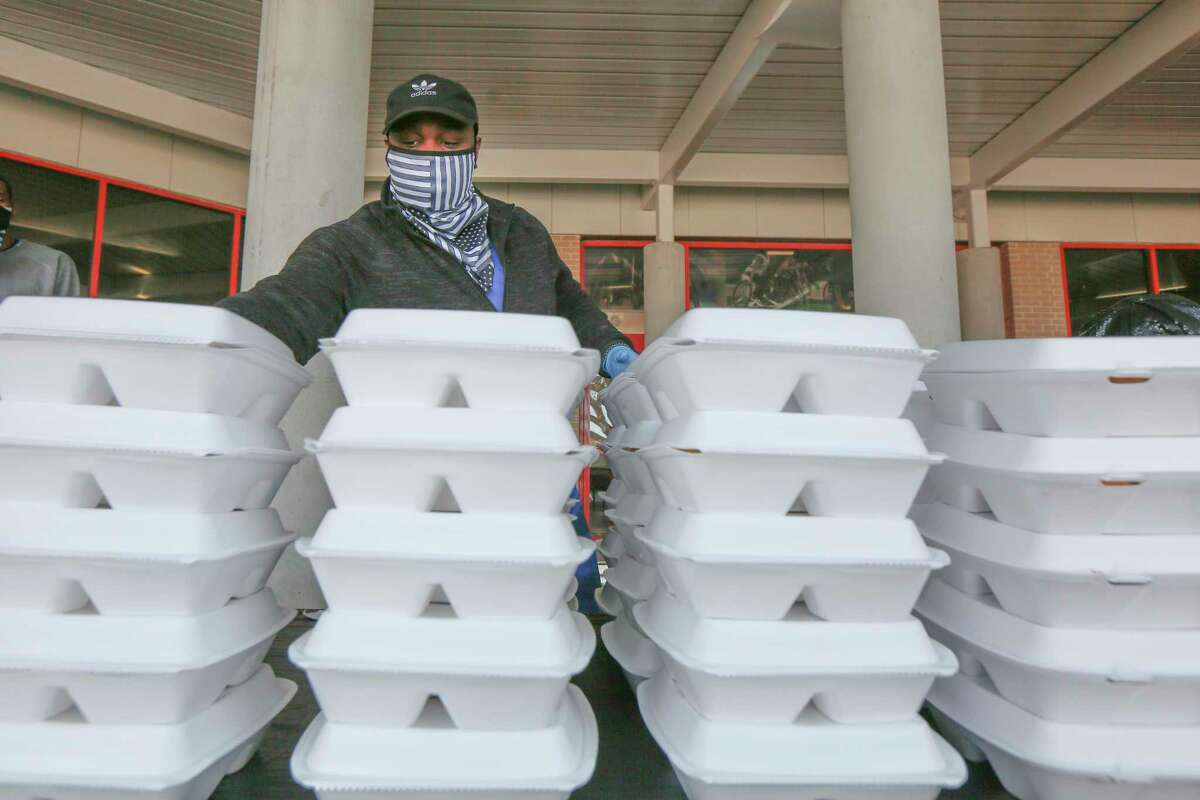 Volunteer C.W. Price stacks Operation BBQ Relief meals before Crowd Source Rescue distributes them Monday, Feb. 22, 2021, in Houston.