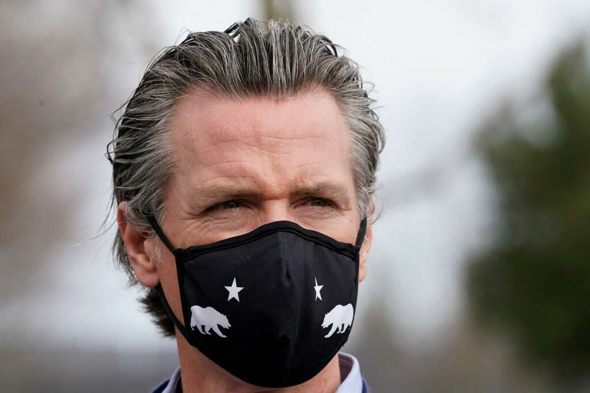 Gov. Gavin Newsom wears a face mask during a visit to a drive-thru COVID-19 vaccination center at Natomas High School in Sacramento, Calif., Thursday, Feb. 11, 2021.