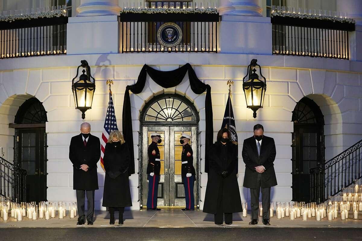 President Biden (left), first lady Jill Biden, Vice President Kamala Harris and her husband, Doug Emhoff, honor the 500,000 Americans who have died from COVID-19 in a ceremony at the White House on Monday.