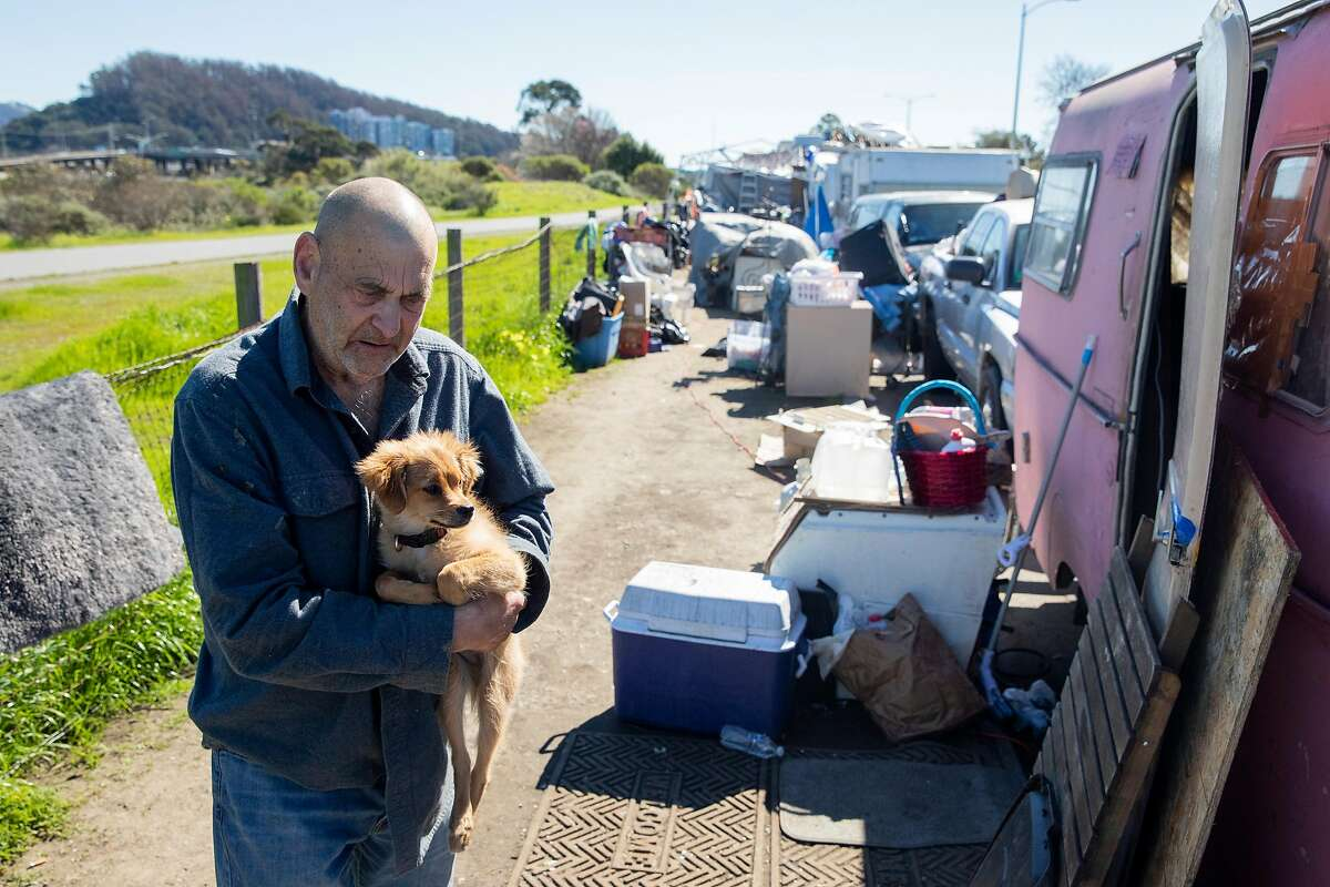 Jim Hauso, 71, and dog Bud visit with a friend at an RV encampment along Rydin Road in Richmond.