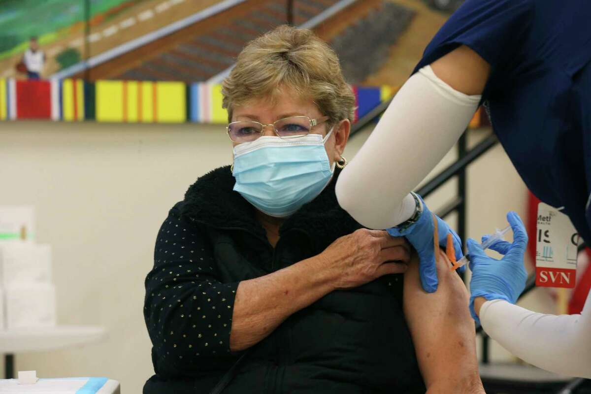 Leticia Guerra gets a Moderna COVID-19 vaccine at the Elvira Cisneros Senior Community Center on Monday, Feb. 22, 2021. Vaccination sites had closed temporarily last week due to the severe weather but resumed Monday.