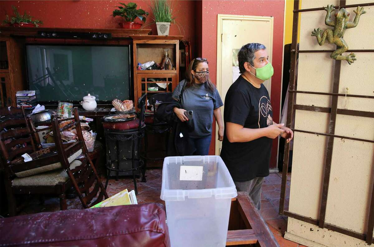 Anthony Leahman and his daughter Michelle De Los Santos inspect the damage in his home of 21 years that caught fire during last week's winter storm. Leahman and his wife, San Juana, were able to save their eight rescue dogs when they escaped the fire.