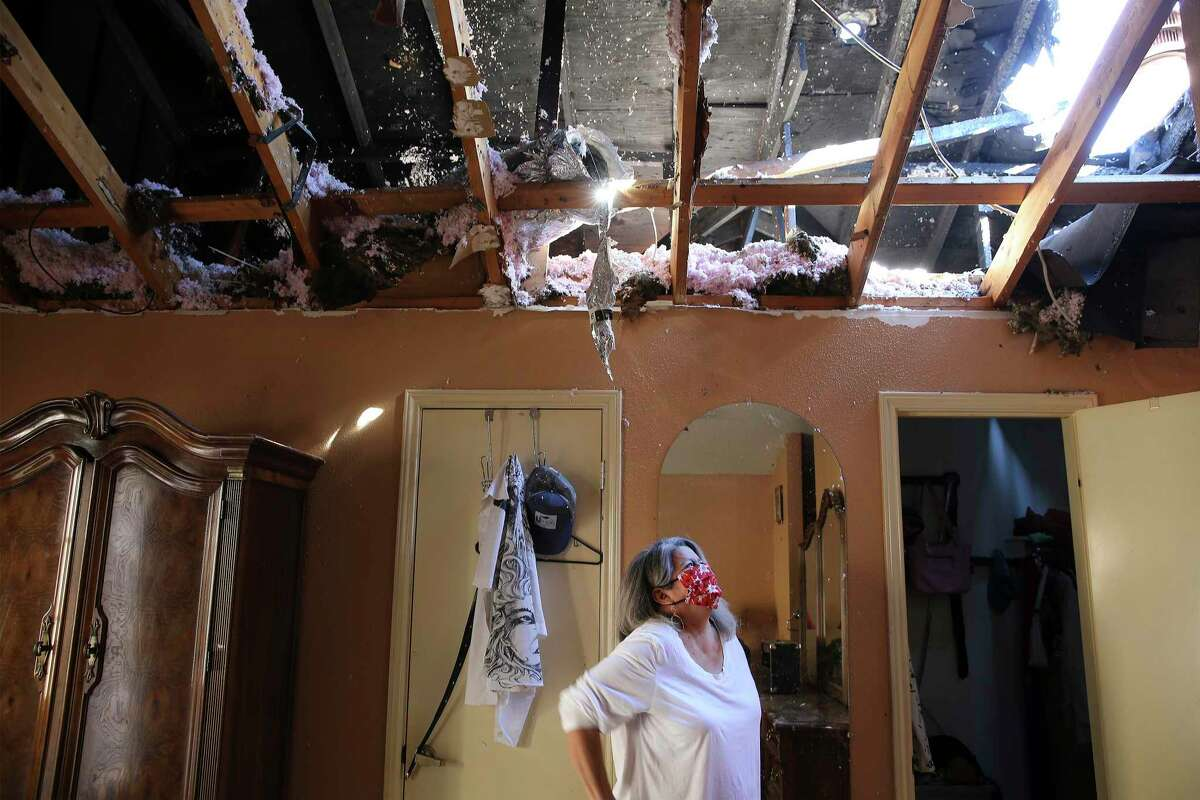 San Juana Leahman looks at the damage in her bedroom of her home of 21 years that caught fire during last week's winter storm.