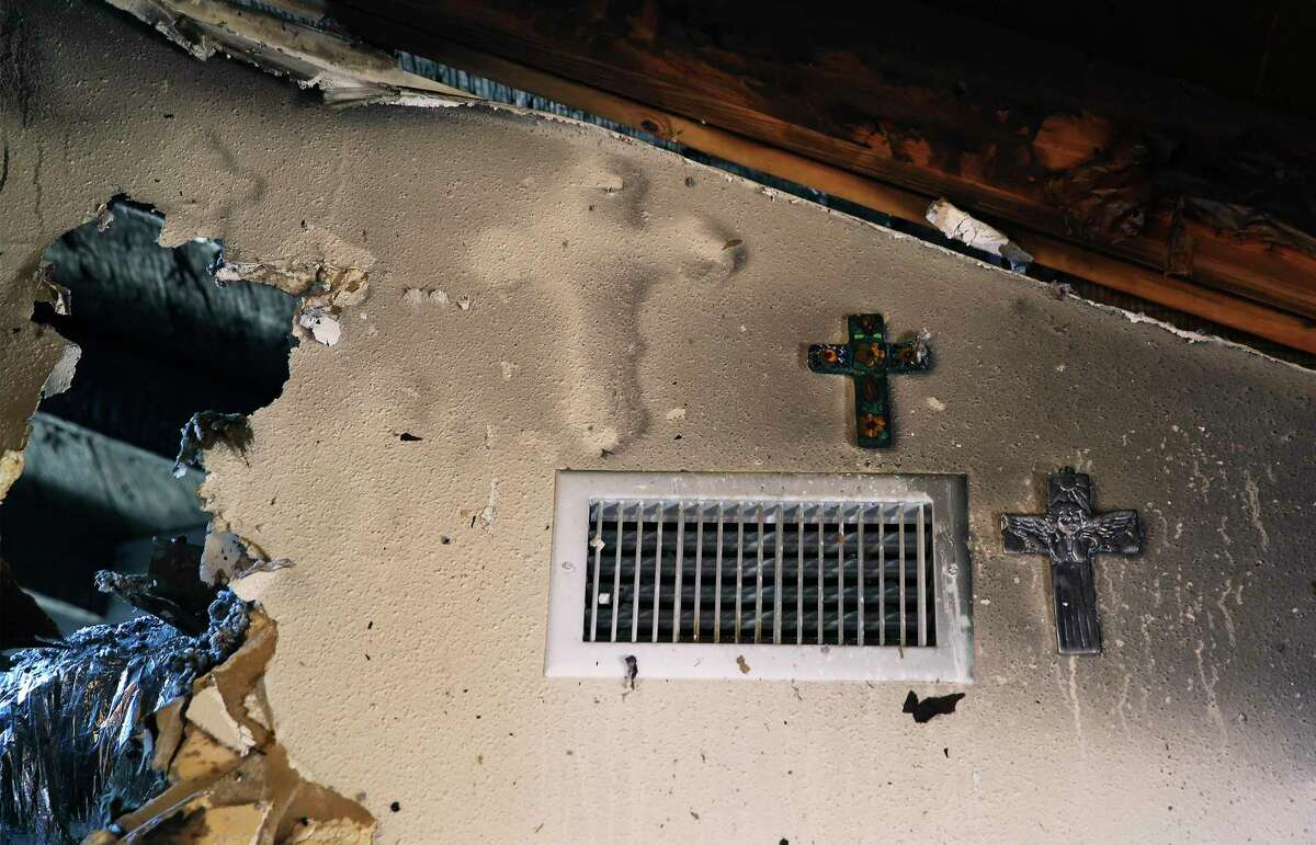 A burned imprint of a cross is seen on a smoke and fire damaged wall in Anthony and San Juana Leahman's home.