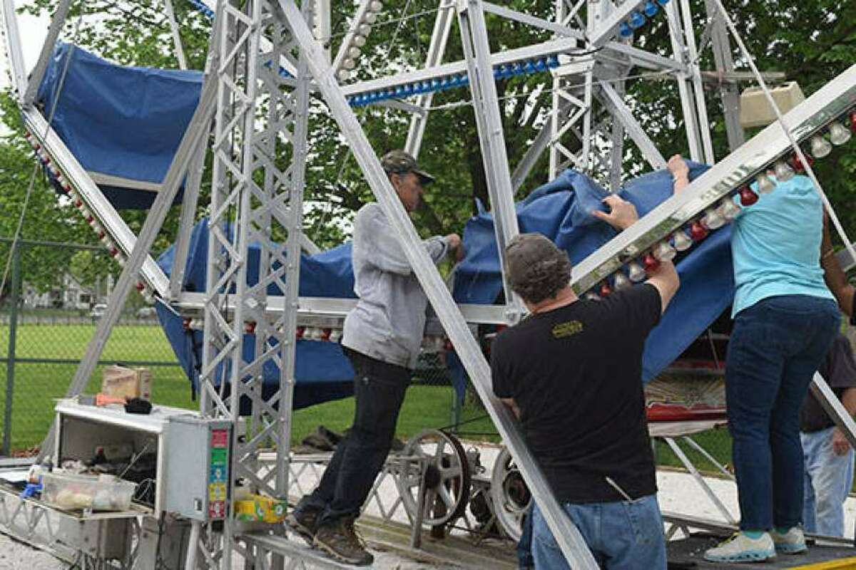 """Volunteers prepare an Eli Bridge Co. Ferris wheel in Community Park for riders. The company's creations are among those in contention for the title of """"coolest thing in Illinois."""""""