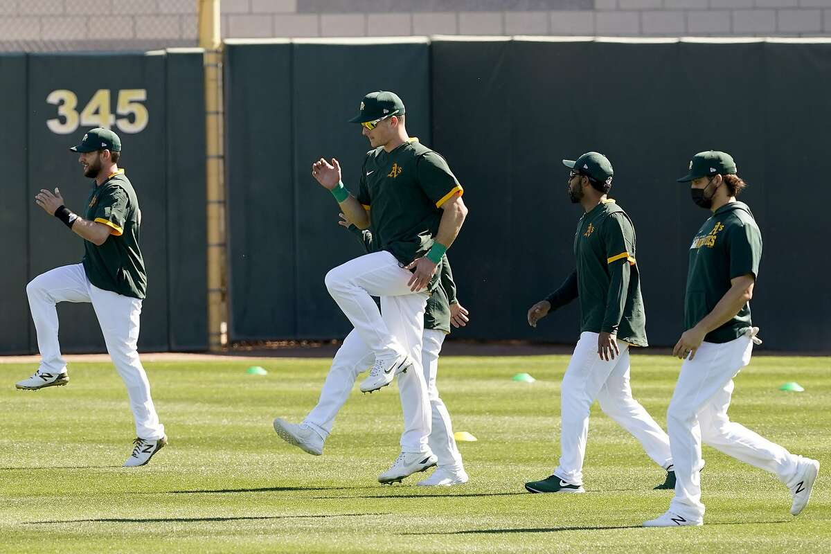 Matt Chapman, center and other Oakland Athletics players warm up during a spring training baseball practice, Monday, Feb. 22, 2021, in Mesa, Ariz. Chapman told sportswriters that at the beginning of spring training 2021 he is feeling good and ready to play following offseason hip surgery.