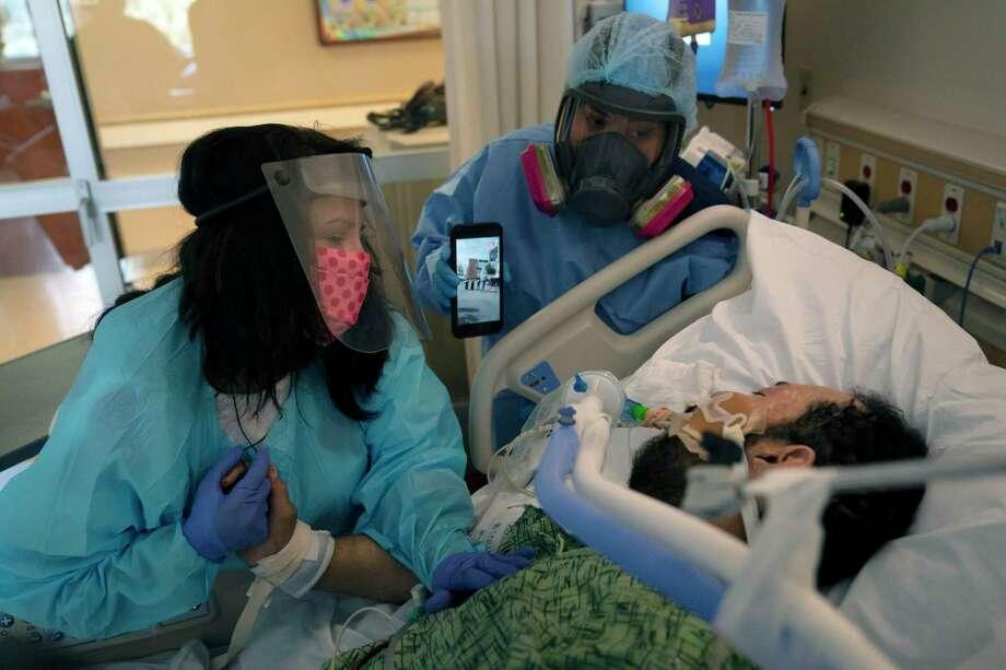 Patty Trejo, de 54 años, toca el rostro de su esposo intubado el lunes 15 de febrero de 2021 en una unidad de COVID-19 en el Centro Médico St. Jude, en Fullerton, California. Photo: Jae C. Hong /Associated Press / Copyright 2021 The Associated Press. All rights reserved