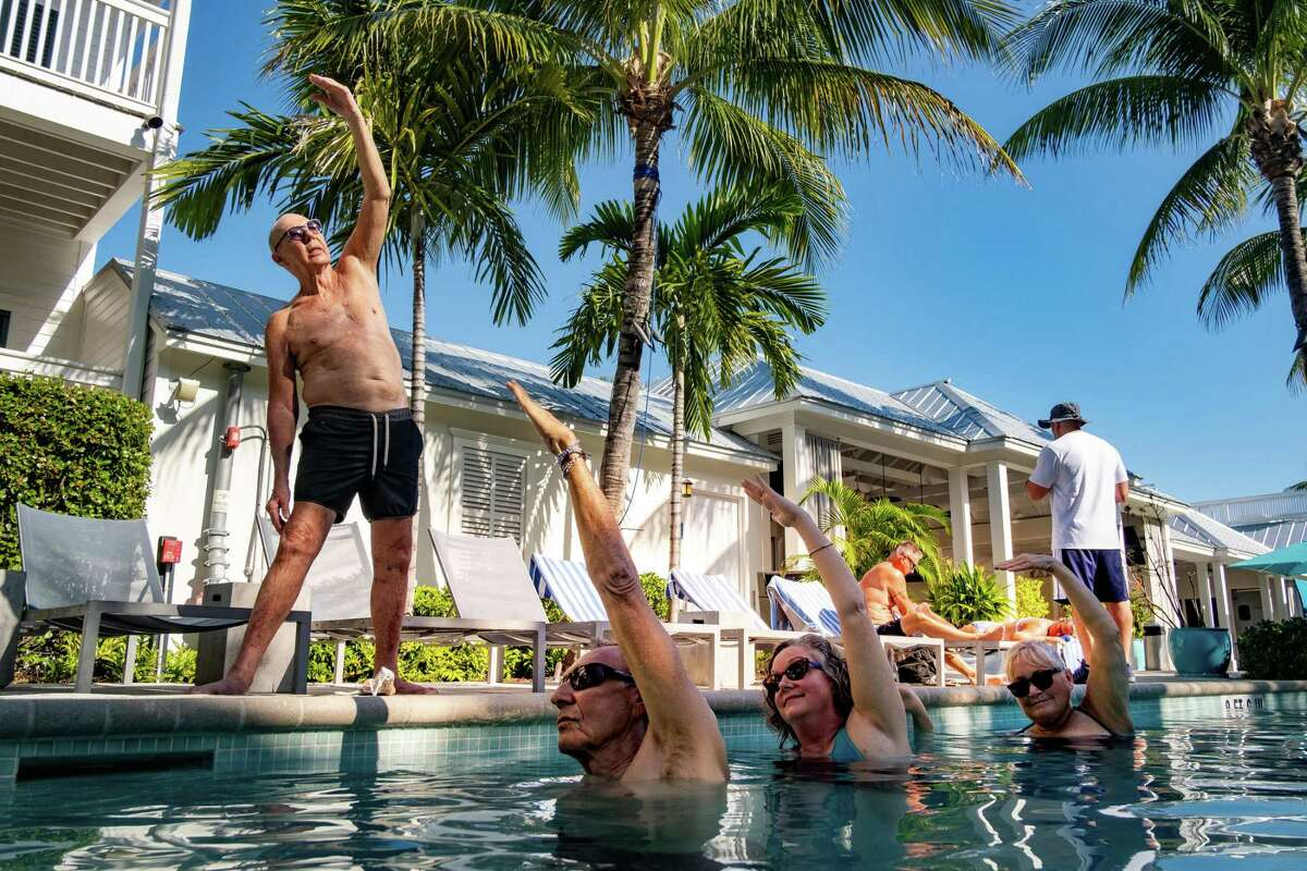 Instructor Peter Rogers teaches an aqua yoga class, put on hiatus during the coronavirus pandemic, at the Marker Key West Harbor Resort in Key West, Fla., on Feb. 13, 2021. Across the United States, older people have been among the first in line to receive their COVID-19 vaccinations, and data shows older travelers are leading a wave in new travel bookings. (Mark Hedden/The New York Times)