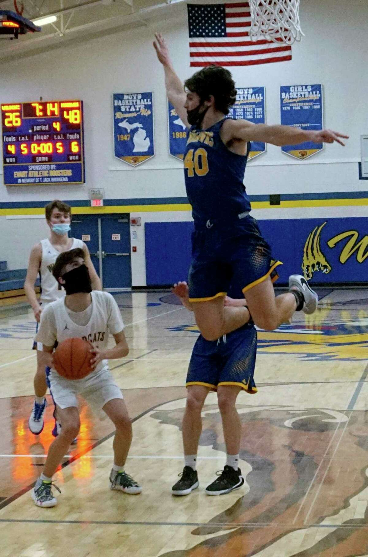 Carter Veldkamp, of Morley Stanwood, goes airborne in an attempt to block a shot from Evart's Cannan Morgan on Monday evening. (Pioneer photo/Joe Judd)
